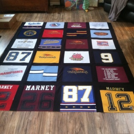 An in-progress picture of a hockey quilt. Look carefully and you can see I incorporated his socks!